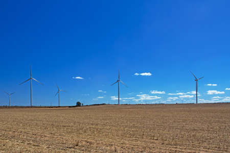 Landscape of wind turbines in dry field after harvest and blue cloudy sky near Hopefield, South Africa Stock Photo