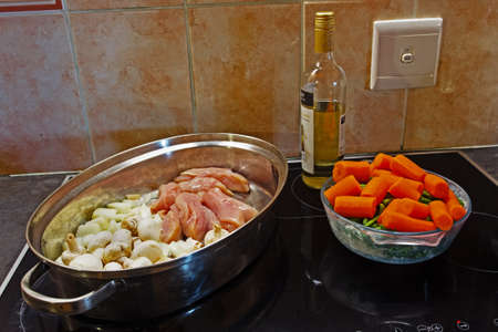 Ingredients for chicken casserole including chicken, mushroom, onion, carrot, beans and wine