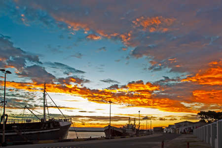 Flaming yellow sunset in harbour with row of fishing boats moored at quayside, Western Cape, South Africa