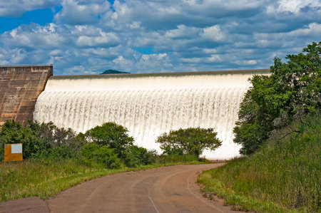 Water flowing over concrete dam spillway