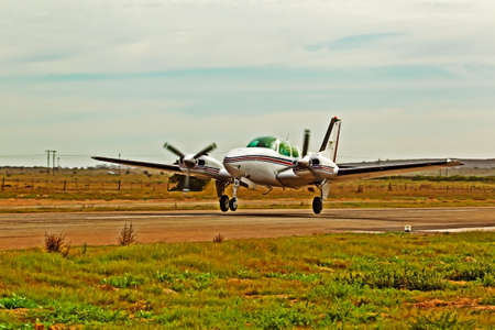 White twin engine aircraft taking off Stock Photo