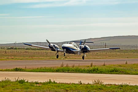 Blue and white twin engine aircraft taking off Stock Photo