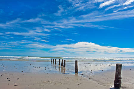 Wide beach with row of posts and blue cloudy sky in Western Cape, South Africa