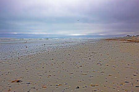 Beach with dark, nimbostratus clouds covering sky Stock Photo