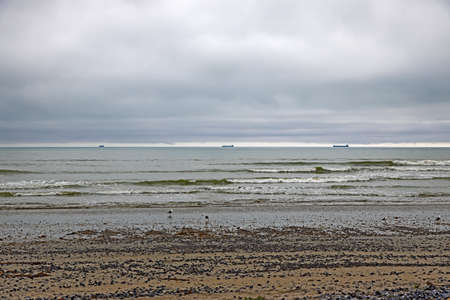Three distant cargo ships and low-level cloud Stock Photo