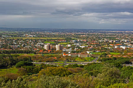 View of Southern suburbs in Cape Town Suburbs from Devils Peak with dark cloudy sky
