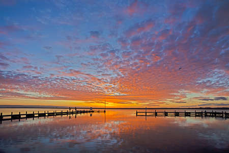 Red, orange and yellow sunset over jetty on the Berg River in Western Cape, South Africa