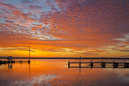 Orange and yellow sunset over jetty on the Berg River in Western Cape, South Africa Stock Photo