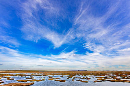 Skyscape of blue sky and clouds above salty marsh on Berg River, Western Cape, South Africa
