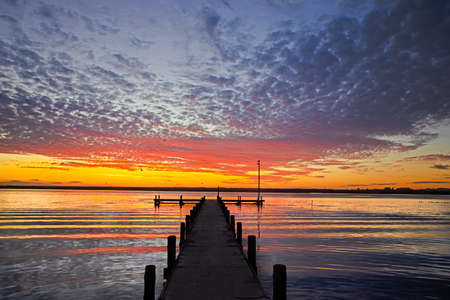 Red and Yellow sunset above perpendicular jetty on Berg River in Western Cape, South Africa Stock Photo