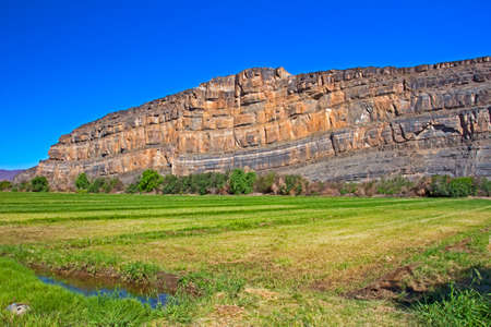 Irrigation canal running along green irrigated field with stony mountain in background Northern Cape, South Africa Stok Fotoğraf