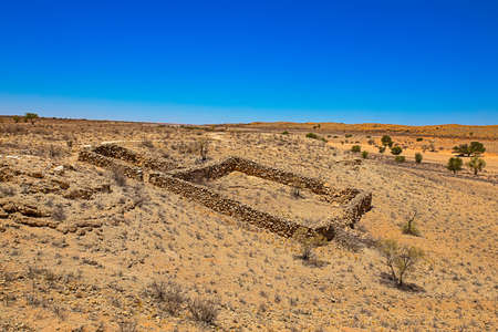 Ancient stone sheep pen built on sloping hill above dry river in Kalahari Desert, Northern Cape, South Africa