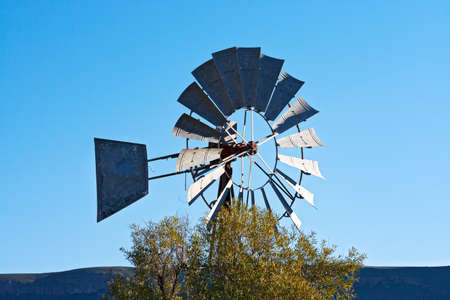 Old water pumping windmill with metal vanes against blue sky in South Africa