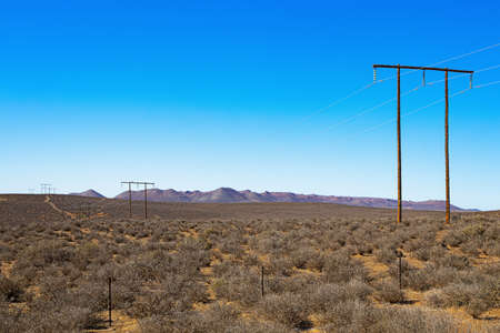 Wooden high voltage transmission line through arid Karoo region of Northern Cape, South Africa