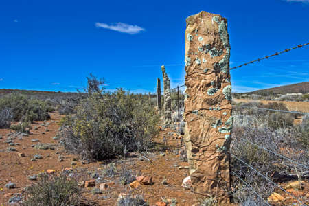 Old stone fencing pillars incorporated as part of barbed wire fence in Karoo, , Northern Cape, South Africa Stockfoto