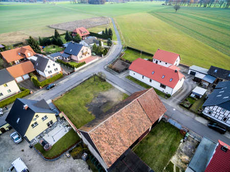 Building development with single-family houses on the edge of a village near Wolfsburg, Germany, aerial view with drone, with fields and meadows in the background, oblique shooting angle