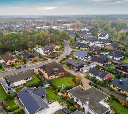 Suburban settlement in Germany with terraced houses, home for many families, aerial photograph taken at a slanting angle with the drone, dramatic sky