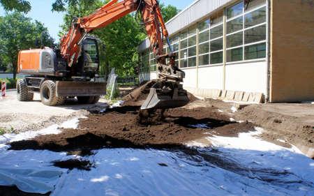 有毒な土壌汚染に対する保護としてジオテキスタイルのカバー。掘削機でのきれいな土壌の適用
