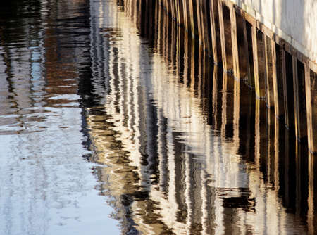 Water reflections of the sheet piling and commercial buildings in a quiet flowing river , Aller in Gifhorn, Germany Stock Photo
