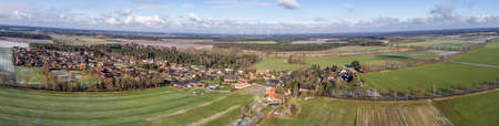 Aerial landscape photo, panoramic view of a small village between fields and meadows, as banner for a blog or website.