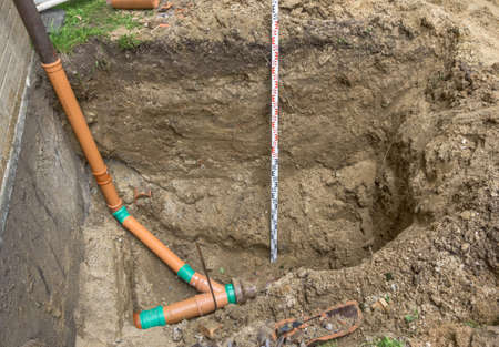 Laying a sewage pipe at the corner of a terraced house in Germany, construction site Stockfoto