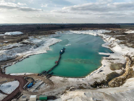 Aerial photo of one of the quartz quartz quartz quarry mining ponds with a suction dredger in the foreground and a dramatic sky. Made with drone