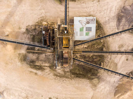 Vertically taken aerial photograph with the view of a large processing machine when used in a sand quarry, to divide the dredged material into different fractions, abstract aerial view, drone shot