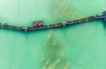 Aerial view of the long boom of a suction excavator in a quartz quarry for the excavation of white sand, made with drone