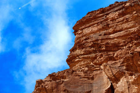 Cut monolith in the desert of the nature reserve of Wadi Rum, in the sky with an airplane that generates contrails, Jordan, midde east Banco de Imagens - 103185358