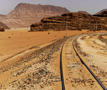 One-track railway with large rock formations in the background, in the desert of Wadi Rum, Jordan, middle east