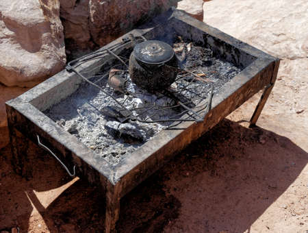 Bedouin stove with a kettle boiling water by the stairs to the Al-Deir Monastery in Petra, Jordan