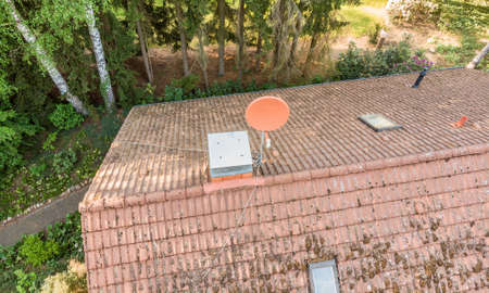Overflight of the roof of a detached house to check the condition of the satellite antenna for the reception of television and Internet, aerial view made with drone