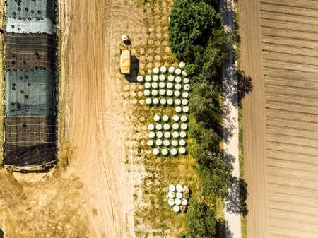 Aerial view of a farm warehouse, vertical photographed round silage bales wrapped in foils, made with drone Banco de Imagens