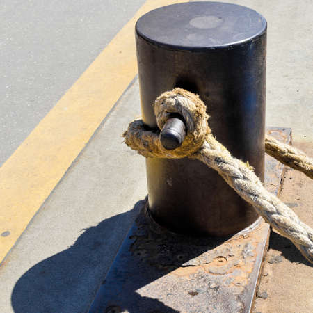 Bollard on a rusty iron plate with a weathered thick rope of hemp, port of Hamburg