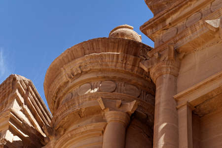 Photo taken at an oblique angle of a section of Al-Deir, the so-called monastery, in the necropolis of Petra, Jordan