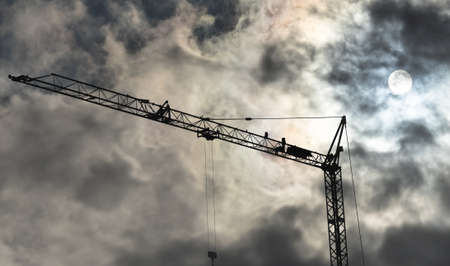 High black construction crane in front of a dramatic threatening sky with translucent sun behind the clouds, germany Banco de Imagens