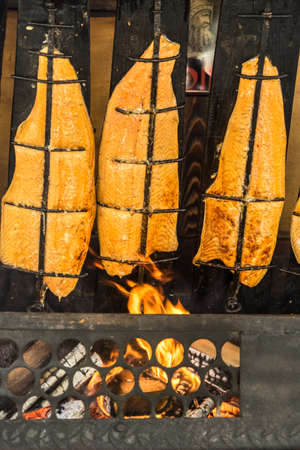 Preparation of flame salmon over the open fire of an open fireplace loaded with wood, Germany Banco de Imagens