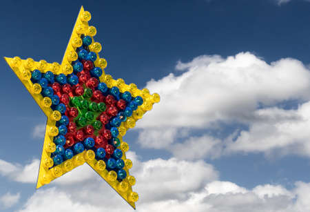 Large colorful star of differently colored lamps exempted in front of a blue sky with clouds, illustration