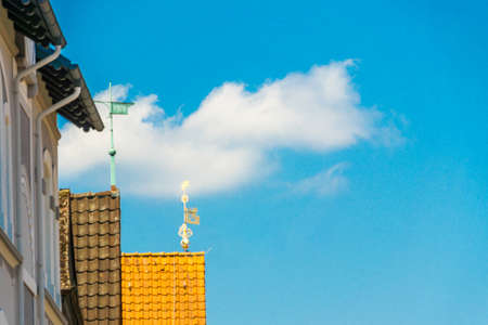 Artistic abstract picture of a small cloud in the blue sky above the roofs of medieval houses in a small town, Gifhorn, Germany Stock Photo