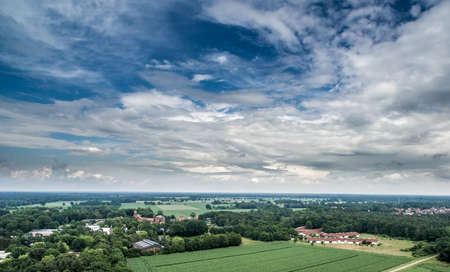 Aerial view of an area of arable land at the edge of a village with connected forest areas and trees along a road in Germany, dramatic sky, made with drone