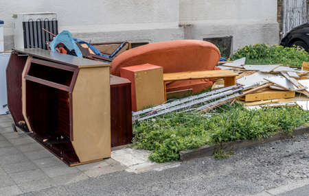 Bulky waste with cupboards, a sofa and furniture on the lawn in front of an apartment building, germany 스톡 콘텐츠