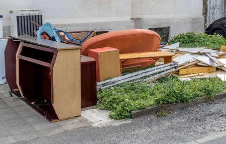 Rifiuti ingombranti con armadi, un divano e mobili sul prato davanti a un condominio, germania