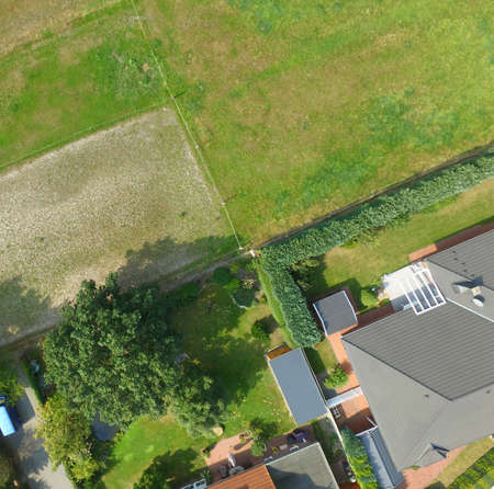 Plots with a meadow, a lawn, a detached house and a terraced house adjoin at one point, plot boundaries look like an abstract cross, Germany Stok Fotoğraf