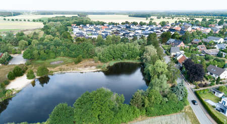 Aerial view of a suburb behind a small lake and a wooded area, with detached houses, semi-detached houses and terraced houses with small front gardens and green lawns in northern Germany Stock Photo