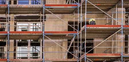Facade with scaffolding and a worker working on the renovation, backside of the building