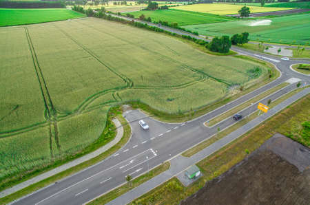 Aerial view of a road with signs and guidelines for traffic between a new development area for an industrial estate and an arable area with green wheat, Germany