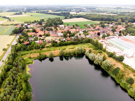 Aerial view of a small German village behind an artificial lake, which was created by sand mining for a concrete plant, made with drone