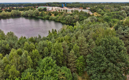 Almost right-angled lake, residual hole of a former sand quarry, surrounded by dense tree population near Gifhorn, Germany