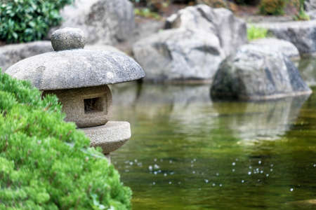 Pond in a Japanese garden with a traditional stone lantern in the foreground, low depth of field