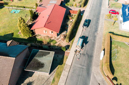 Aerial view of a simple detached house on an asphalted grey village road, on which a road worker carries out maintenance work, made with drone Banco de Imagens